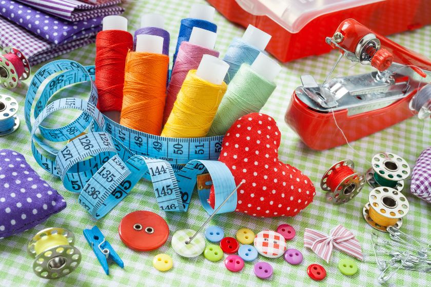 30832607 - tailor items: spools of colorful thread, buttons, fabrics, measuring tape, pincushion, small sewing machine and measuring tape